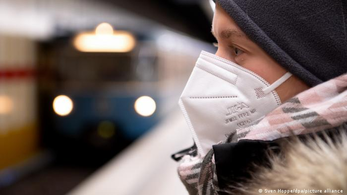 Woman standing on subway platform, wearing an ill-fitting N95 mask