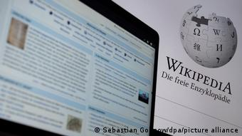 Symbolbild 20 Jahre Wikipedia - Auf einem Monitor ist die geöffnete Hauptseite der deutschsprachigen Wikipedia zu sehen, im Hintergrund steht unter dem Logo Wikipedia. Die freie Enzyklopädie.