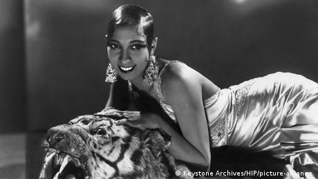 Josephine Baker young woman with short slicked back hair lsmiles propped onna tiger skin rug