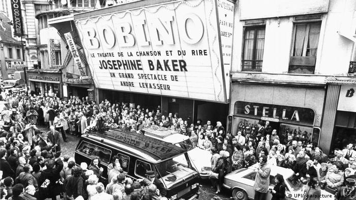 Tausende Menschen stehen am Straßenrand, ein Leichenagen fährt am Bobino Theater in Paris vorbei
