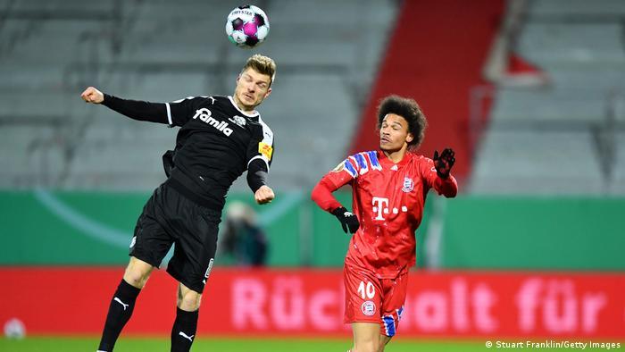 Alexander Muhling of Holstein Kiel beats Bayern Munich's Leroy Sane to a header