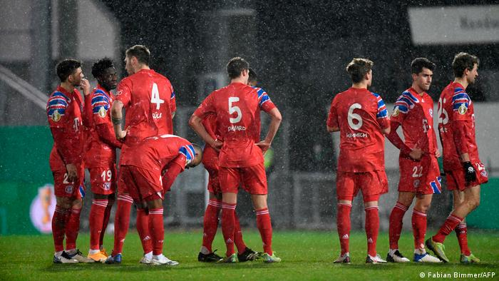 Bayern Munich's players watch on during the penalty shootout at Holstein Kiel.