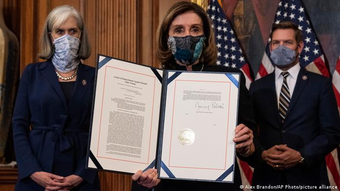 House Speaker Nancy Pelosi holds the article of impeachment against President Donald Trump after signing it
