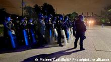 Police stand ready to block the way of a group of migrants walking along a highway hoping to reach the distant U.S. border, on the outskirts of San Pedro Sula, Honduras, shortly after setting off, Wednesday, Jan. 13, 2021. About 200 migrants began walking toward the border with Guatemala, two days before a migrant caravan was scheduled to depart the city. (AP Photo/Moises Castillo)