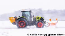 Баварский фермер Кристиан Бецольд убирает на своем тракторе дорогу около Байройта