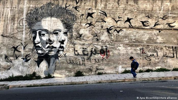 A child walks past a mural, painted on a wall in Amman, Jordan.