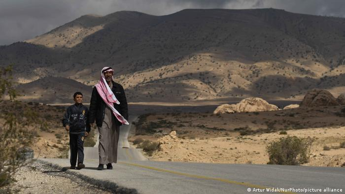 A man with young boy walk on the desert road near a Bedouin village in Jordan.