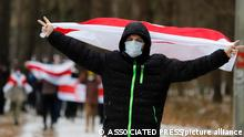 A demonstrator wearing a face mask to help curb the spread of the coronavirus waves an old Belarusian national flag during an opposition rally to protest the official presidential election results in Minsk, Belarus, Sunday, Dec. 13, 2020. Protests in Belarus have continued for almost four months after President Alexander Lukashenko won his sixth term in office in an election the opposition says was rigged. (AP Photo)