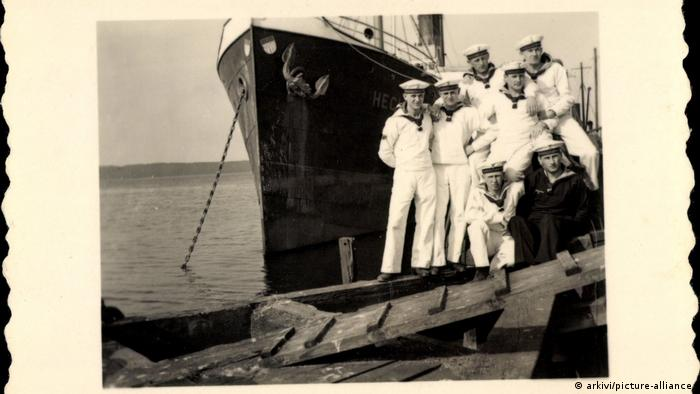 Sailors in front of a ship