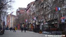 Passanten in der mit serbischen Fahnen geschmückte Haupt-Einkaufsstraße des Nordteils der Kosovo-Stadt Mitrovica