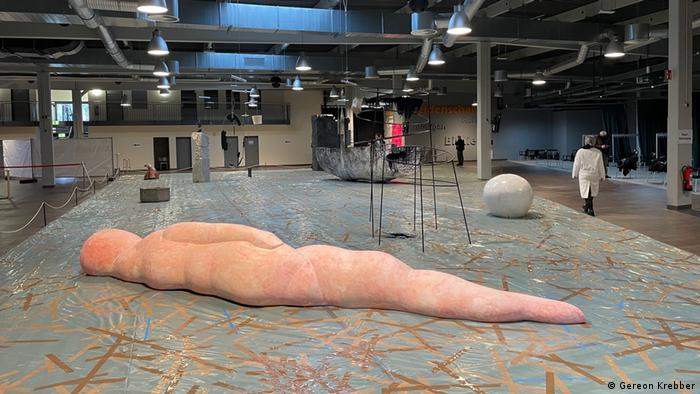 Several sculptures in a large hall, a pink human-like form lying on the ground at the front