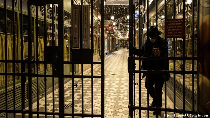 A man closes the gate of a covered passage in Paris on December 15, 2020, as a new 8:00 pm-6:00am curfew is implemented in France