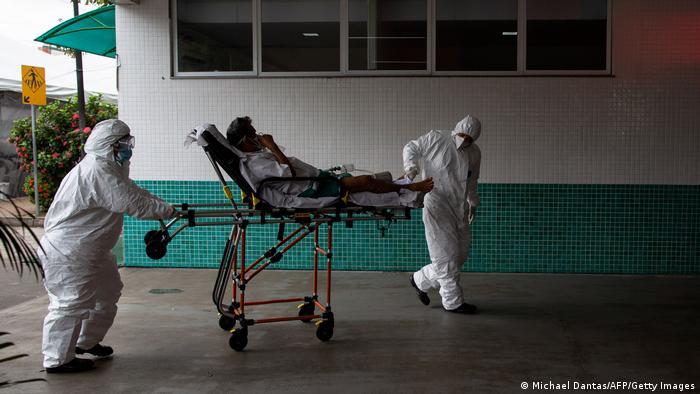 Funcionários de saúde carregam paciente em maca em hospital de Manaus
