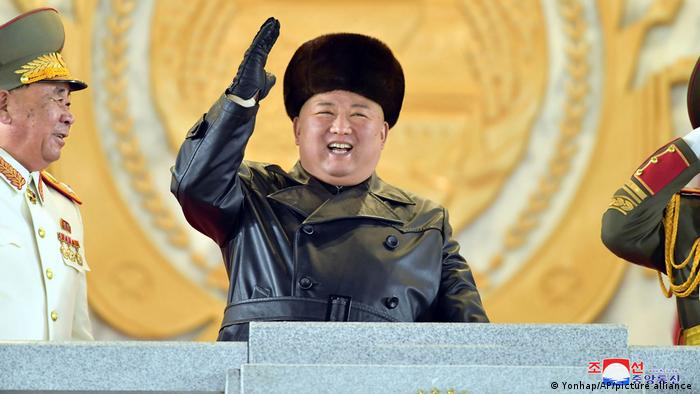 North Korean leader Kim Jong Un waves wearing a black fur hat as Kim attended a military parade