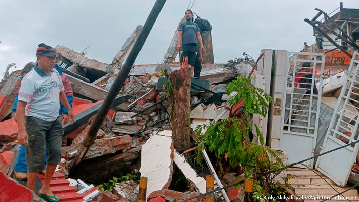 Two people stand on rubble of houses surveying the damage