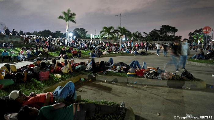 Hondurans rest outside a bus station before taking part in a new caravan of migrants