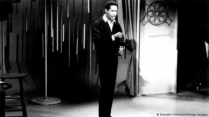 Der Sänger Sam Cooke steht im schwarzen Anzug und weißem Hemd.auf einer Bühne