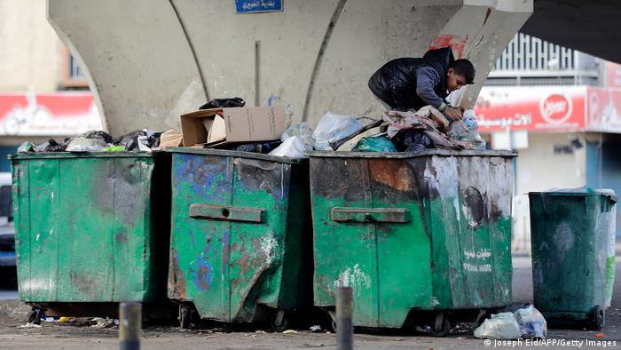 A child rummaging in garbage containers