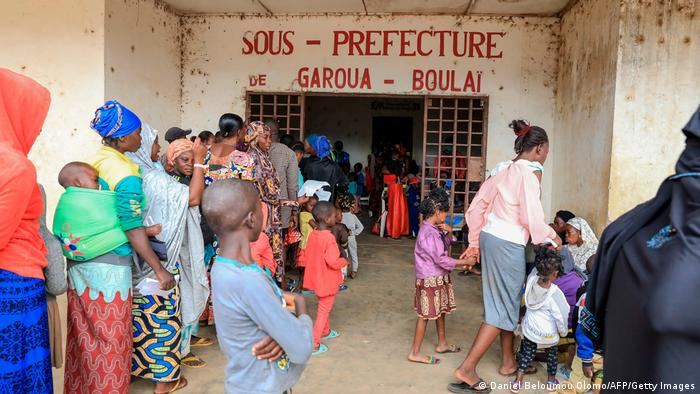 Refugees from CAR line up before an administrative center in Cameroon
