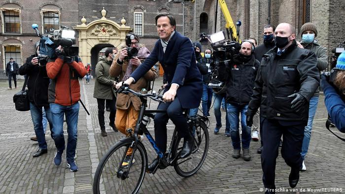 O primeiro-ministro da Holanda, Mark Rutte, conduz uma bicicleta em meio a repórteres