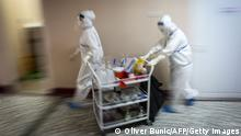 TOPSHOT - Medical workers bring medications to patients suffering from coronavirus disease (COVID-19) inside the Institute for Orthopaedic Surgery Banjica, recently transformed to a COVID hospital, in Belgrade on July 14, 2020. - A candidate for the European Union, this small Balkan country is experiencing a resurgence of the pandemic, which has sparked several evenings of violent demonstrations to denounce the government's management of the health crisis. With 300 new cases now detected every day, Serbia is approaching April levels, at the peak of the first wave. (Photo by Oliver BUNIC / AFP) (Photo by OLIVER BUNIC/AFP via Getty Images)