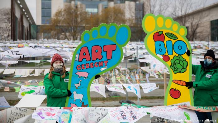 Green-clothed protestors outside the Chancellery displaying giant footprint-shaped placards