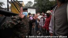 A Guatemalan soldier speaks with Honduran migrants hoping to reach the U.S., at the border in El Florido, Guatemala, Saturday, Jan. 16, 2021. The migrants pushed their way into Guatemala Friday night without registering, a portion of a larger migrant caravan that had left the Honduran city of San Pedro Sula before dawn, Guatemalan authorities said. (AP Photo/Sandra Sebastian)