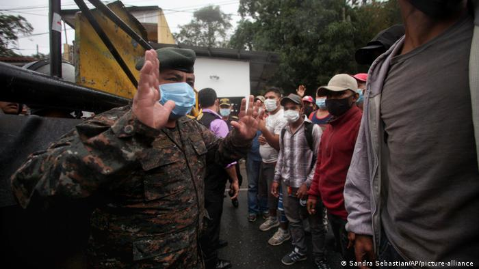A Guatemalan soldier speaks with Honduran migrants hoping to reach the U.S., at the border in El Florido, Guatemala.