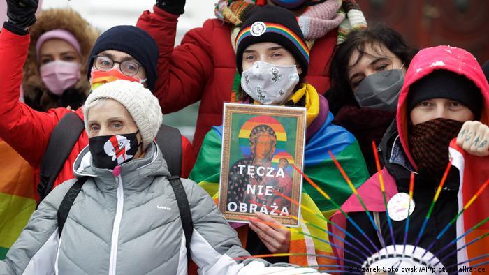 Ein Regenbogen ist keine Beleidigung steht auf dem Plakat mit der angeblich entweihten Schwarzen Madonna von Tschenstochau, dem polnischen Nationalheiligtum, das Demonstrantinnen für dem Gericht in Plock halten