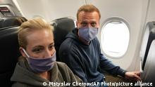 Navalny (right) pictured with his wife Yulia (left) aboard a plane ahead of takeoff in Berlin