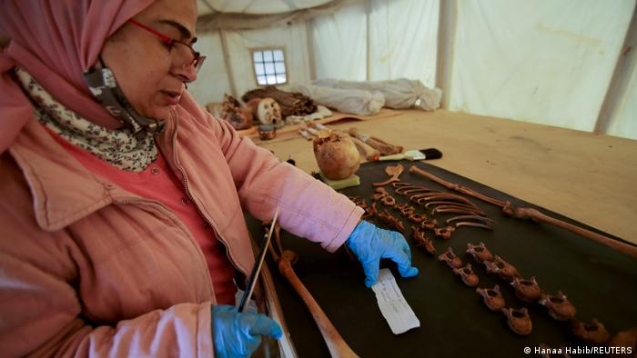 A woman works on artefacts, part of a recent discovery, at the Saqqara necropolis
