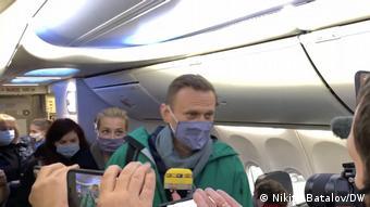 Навальный пытается пройти к своему месту в самолете