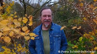 A photo of Dr. Schmiedel outdoors next to fall leaves