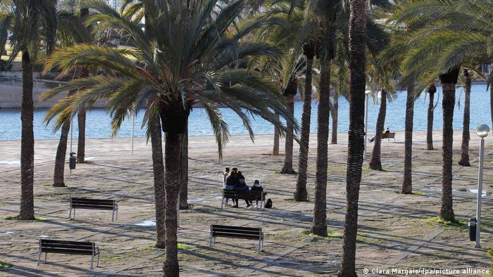 People sitting on a park bench in Palma on the Spanish island of Mallorca