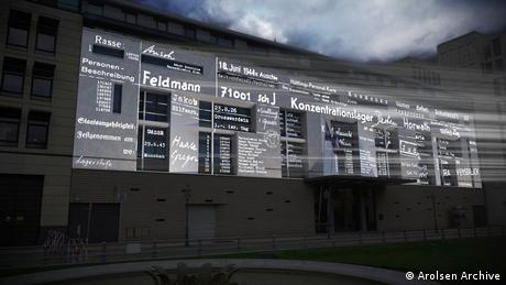 #everynamecounts Arolsen Archive | names and descriptions projected on the wall of a building
