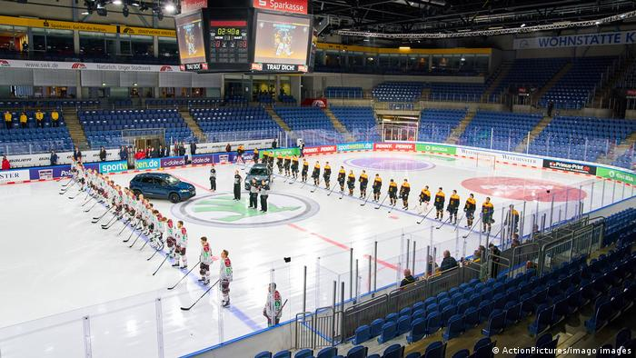 Two ice hockey teams present their anthems as two cars stay in between by sponsor Skoda.