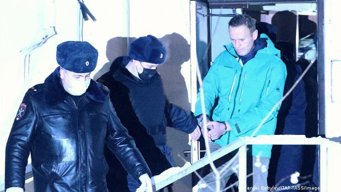 Алексей Навальный в наручниках, в сопровождении полицейских
