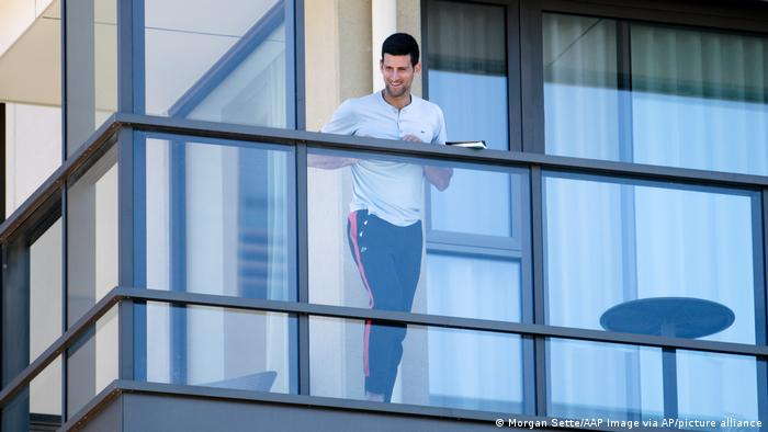 Serbia's Novak Djokovic stands on the balcony at his accommodation in Adelaide