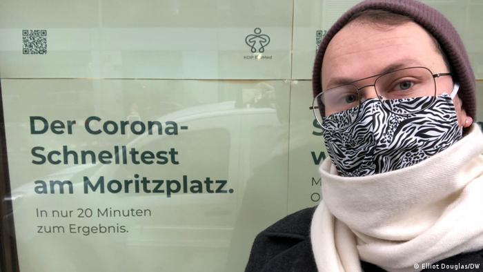 Elliot wearing a mask, hat and scarf, standing in front of a sign advertising a quick test center in Berlin