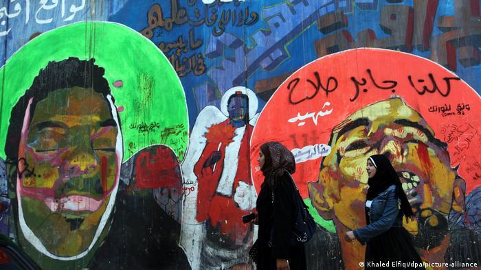 Sebuah grafiti di dinding Kairo menunjukkan seorang anak laki-laki dengan mata tertutup dan di sampingnya adalah seorang wanita yang memegang mawar, diikuti oleh kepala seorang pria yang tampak berteriak