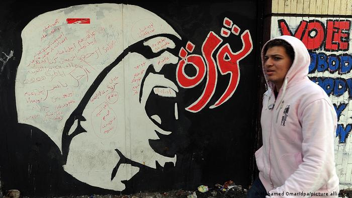 An Egyptian walks past graffiti on a wall in Cairo, with the Arabic word 'revolution'