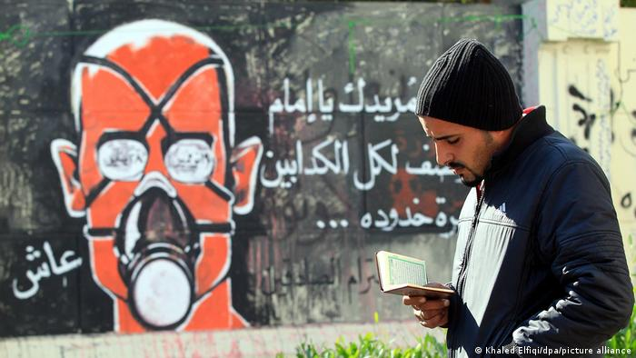 A man stands in front of a street mural in Cairo