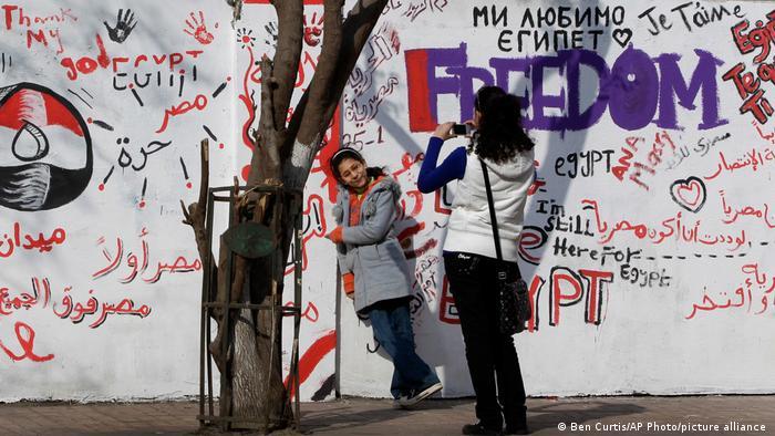 Wanita muda berfoto di depan tembok yang dipenuhi grafiti