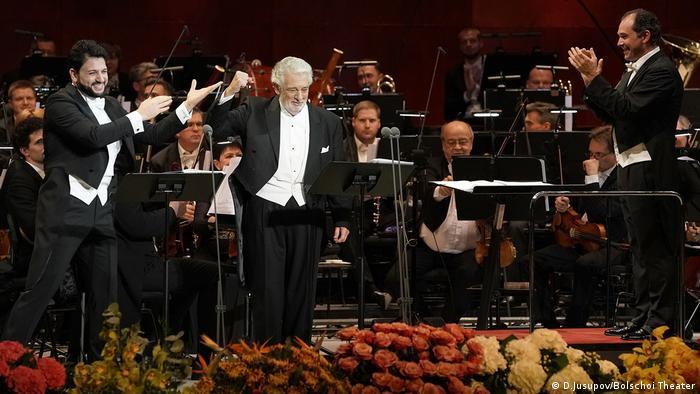 Plácido Domingo steht bei der bei der Operngala in Moskau mit dem Rücken zum Orchester: Ihm applaudieren Tenor und Anna Netrebko-Ehemann Yusif Eyvazov (links), Dirigent Tugan Sokhiev (Rechts)