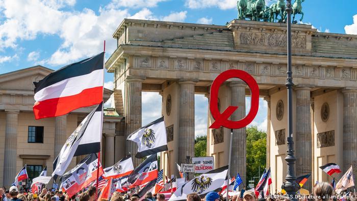 Extremistas exibem símbolo da teoria QAnon durante protesto contra as medidas anticoronavírus em Berlim