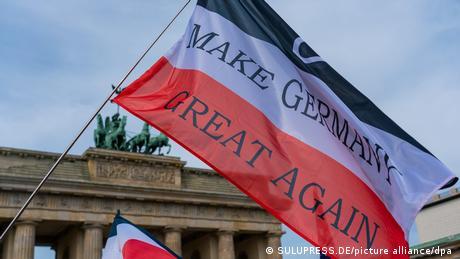 Bandeira Fazer a Alemanha novamente grande em manifestação do movimento ultradireitista Querdenken, com Portão de Brandemburgo ao fundo