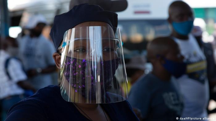 A woman in South Africa wearing a mask and a face shield