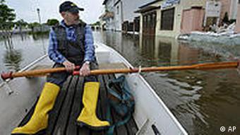 Man rows boat along flooded street