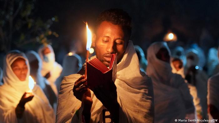 A man reads his bible by candlelight in the early hours of the morning before the Timket celebrations begin.