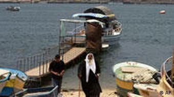 Boote und zwei Männer am Strand, einer in traditioneller Kleidung (Foto: AP)